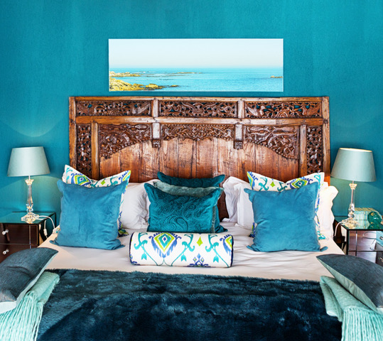 Beautifully dressed bed, with color coordinated fabrics and wall
